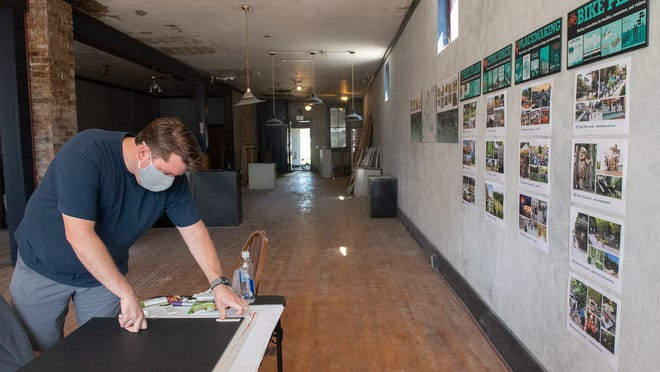 Jason Kentner, the principal architect overseeing Ravenna's Downtown District plan, at a vacant store front filled with drawings and proposal options for the public to express their thoughts and ideas.