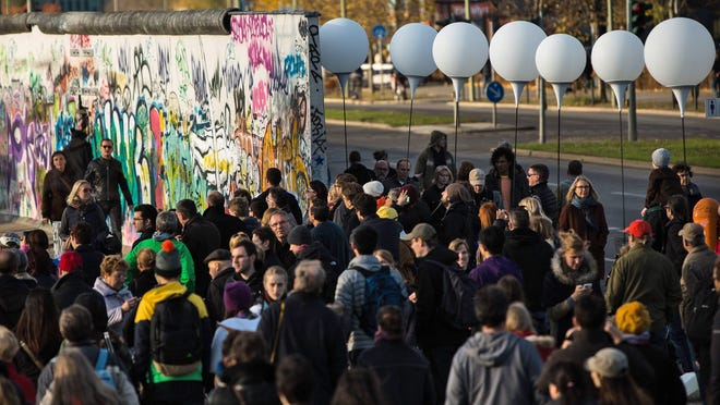 Visitors walk past the balloon poles installed along the East Side Gallery Nov. 8. in Berlin, Germany. Germany launched its celebrations marking the 25th anniversary of the fall of the Berlin Wall when it switched on a so-called 'Border of Lights 2014' in the nation's capital that illuminates where the notorious former Berlin Wall stood.