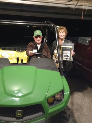 Raffle chairperson Terri Defina presents Clark Waters of Highland with the Gator ATV he won in the Rotary Club raffle.