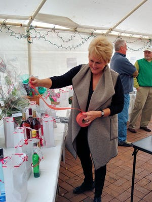 Barbara Harris arranges table during Stone Creek Cove's Brighter Christmas Fund auction