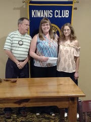 Larry Folwell, past president of the Kiwanis Club of Greater Abilene, presents an award to Susan Jungling and her daughter Laura Jungling of the American Heritage Girls in thanks for their volunteering efforts at the Chili Day Cook-off.