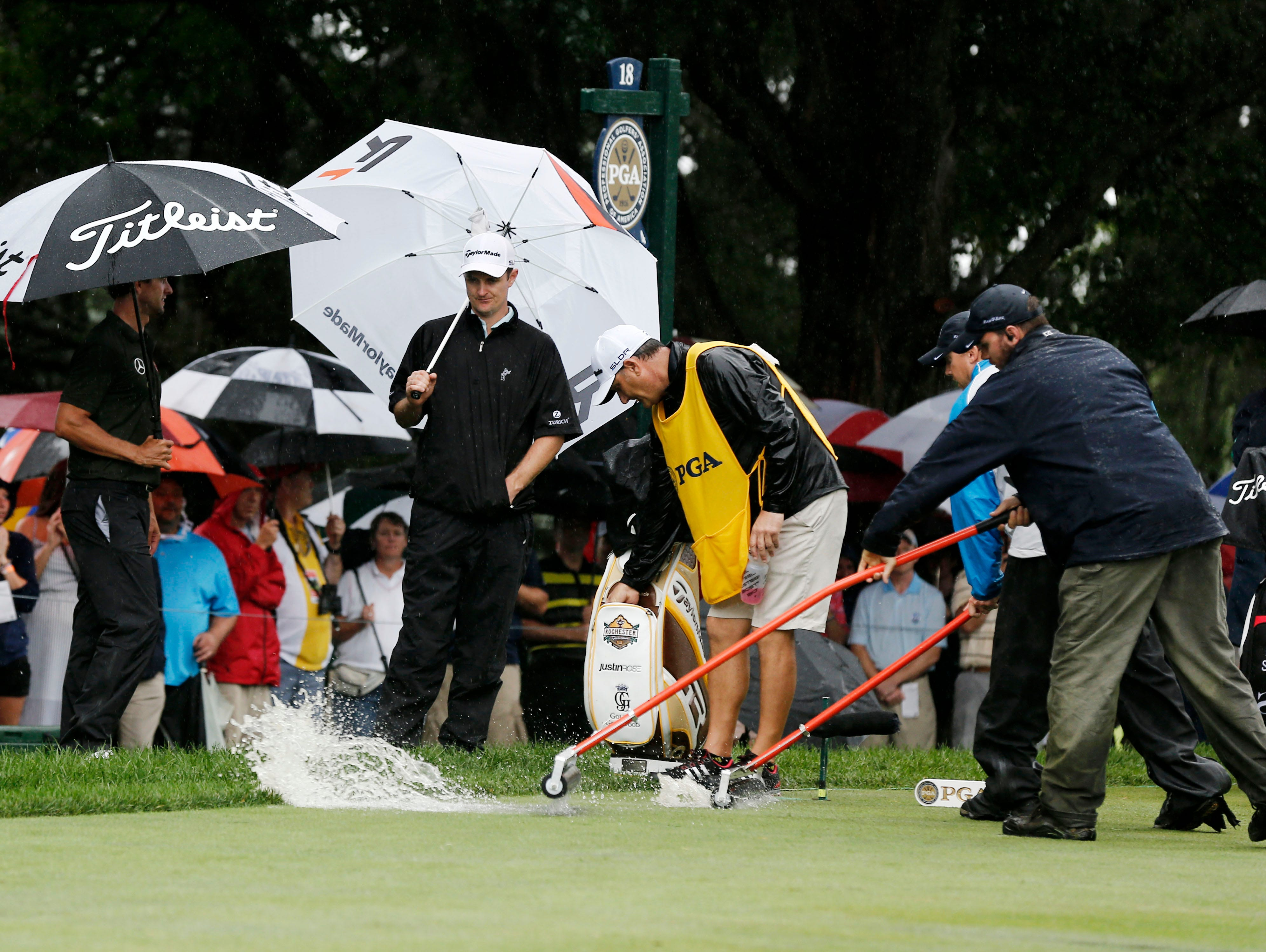 Adam Scott and Justin Rose wait for the ground crew to remove standing water from the 18th tee.
