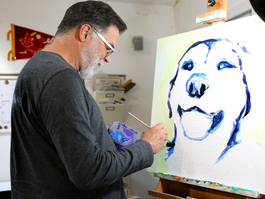 Art Growden a Graphic Designer and Artist, paints a