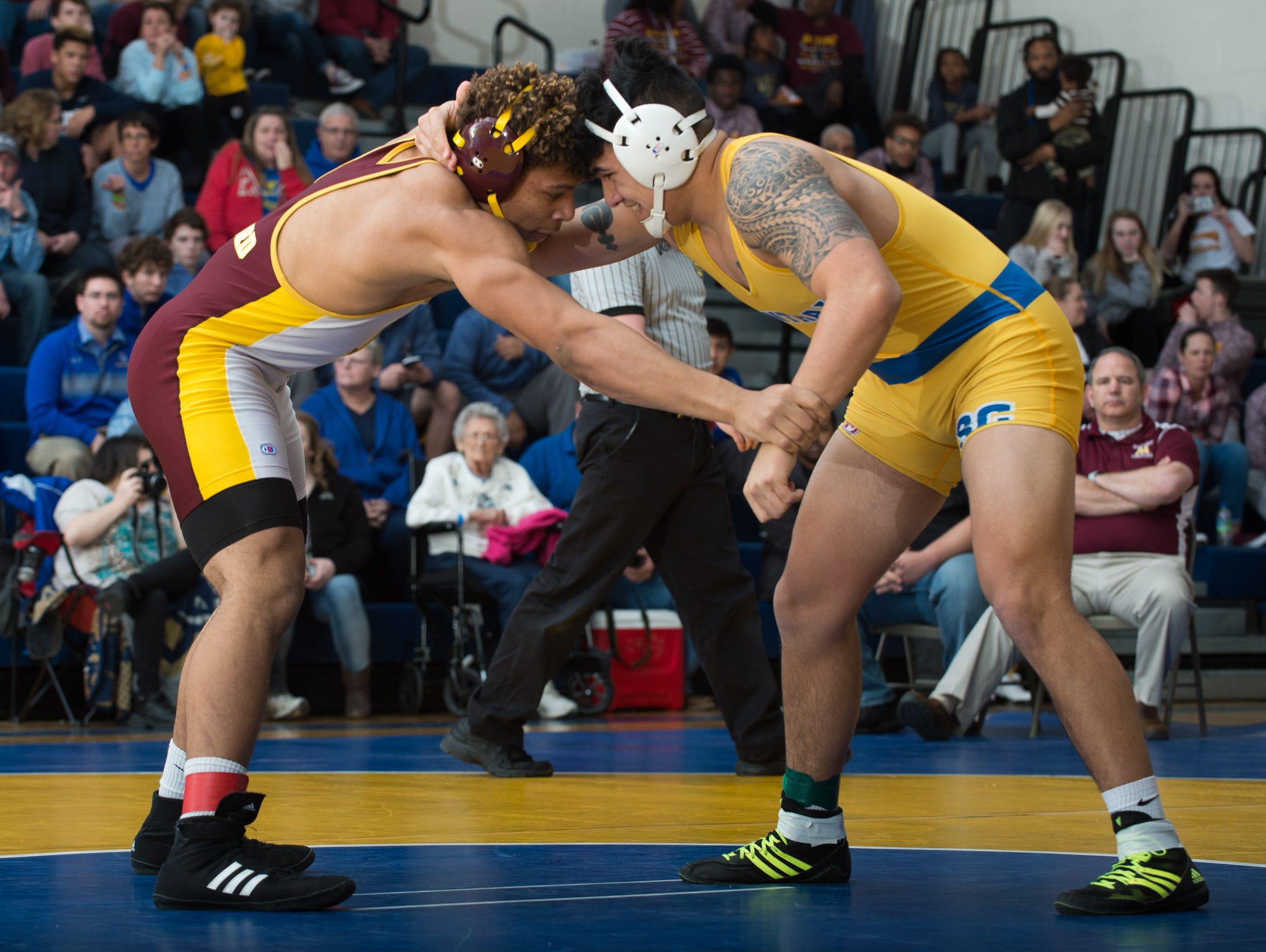 Milford's Dominic Covington, left, and Sussex Central's Johnny Morris battle for position in the 220 pound championship match at the Henlopen Conference wrestling tournament at Sussex Central High School.