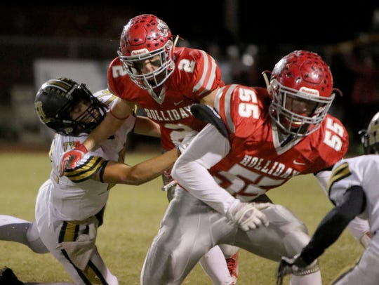 Holliday's Justin Jones is tackled by Henrietta's Jayson