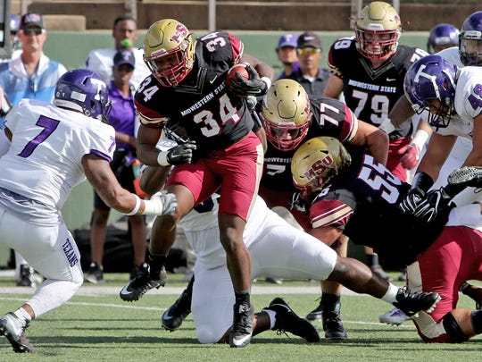 Midwestern State running back Vincent Johnson is tackled by Tarleton State defenders Saturday, Nov. 4, 2017, at Memorial Stadium in Wichita Falls.