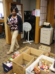 "Marilyn Powell, the circulation/media manager for the New Albany-Floyd County Public Library walks past some of the food items collected in the ""Food for Fines""  forgiveness program."