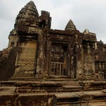 A tourist stands at Angkor Wat in Siem Reap, Cambodia, Saturday, March 21, 2015.