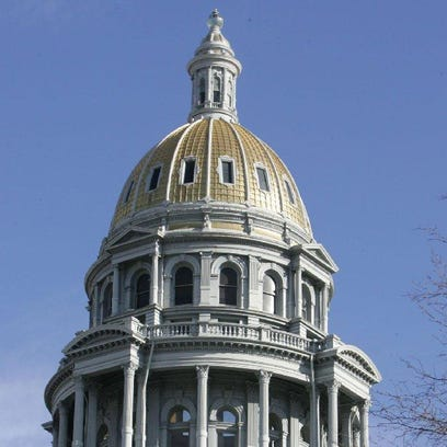 Blue sky surrounds the gold dome of the Colorado State Capitol.