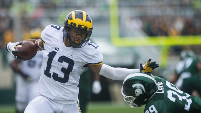Michigan's Eddie McDoom rushes the ball against Michigan State's Justin Layne during their game in East Lansing on Saturday, Oct. 29, 2016.