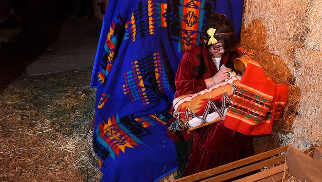 Jennifer Benally and 6-week-old Paisley Nelson take part in the Four Corners Home for Children's annual live Navajo Nativity scene on Dec. 23, 2016, in Farmington.