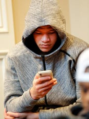 Kentucky basketball's Kevin Knox checks his phone as he and the rest of the team watch the NCAA Tournament selection show at the home of head coach John Calipari Sunday, March 11, 2018, in Lexington, Ky. (AP Photo/James Crisp)