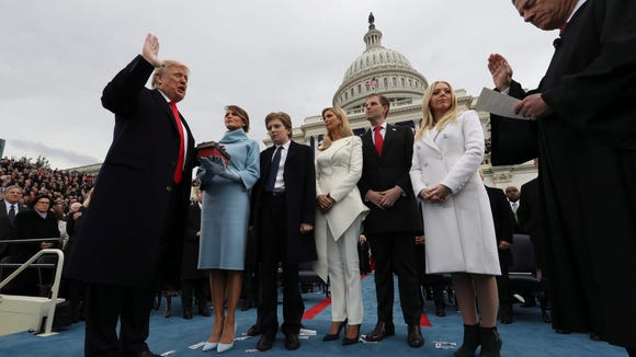 Donald J. Trump takes the oath of office while his