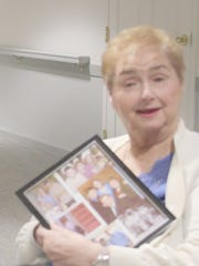 Donna Collins holds a picture frame containing photographs