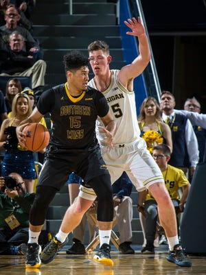 Southern Mississippi forward Eddie Davis III tries to get to the basket while being defended by Michigan center Jon Teske.