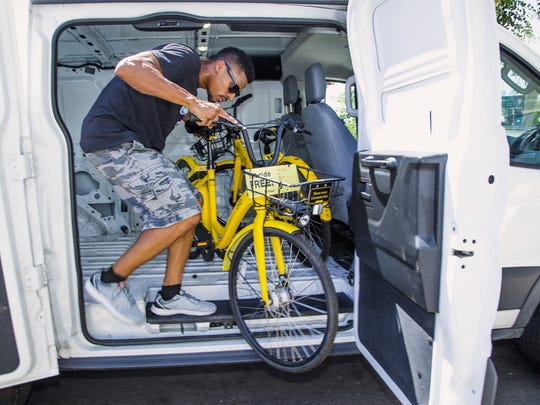 Leroy Carver III, greater Phoenix fleet lead for bike sharing company Ofo, removes a bike from a van at 1260 E. University in Tempe, Friday, July 6, 2018.  The company, allows people to download an app and then check out a bicycle for a fee on the streets of Tempe and other Valley cities. The bikes use GPS to locate them.