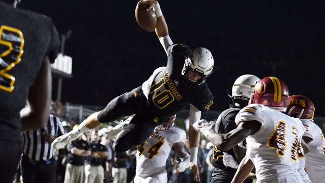 Oak Grove quarterback John Rhys Plumlee dives in for a touchdown in a game against Laurel on Friday in Hattiesburg.