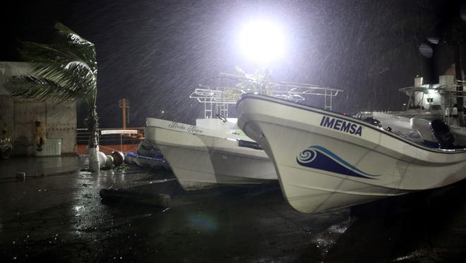 Rain and wind pound boats dragged out of the Gulf onto dry land to protect them, after the arrival of Hurricane Franklin in the port city of Veracruz, Mexico, shortly before midnight on Wednesday, Aug. 9, 2017. Hurricane Franklin, the first hurricane of the Atlantic season, roared ashore north of Veracruz city on a thinly populated part of Mexico's central Gulf coast early Thursday and began weakening as it pounded a mountainous region prone to flash floods and mudslides with rains and heavy winds. Franklin became early Thursday.