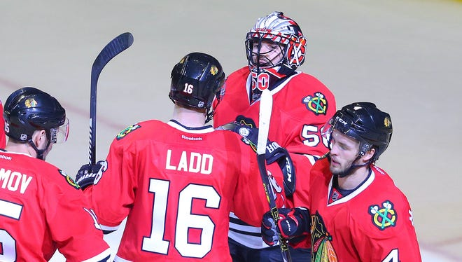 Chicago Blackhawks goalie Corey Crawford receives congratulations from new (and old) teammate Andrew Ladd.