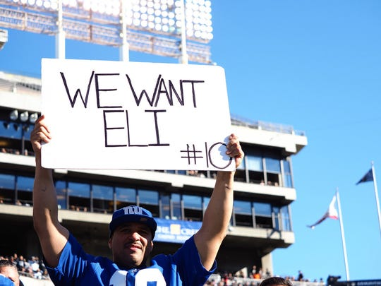 """A fan holds a sign reading """"we want Eli #10"""" for quarterback Eli Manning (not pictured) during the first quarter against the Oakland Raiders at Oakland Coliseum."""