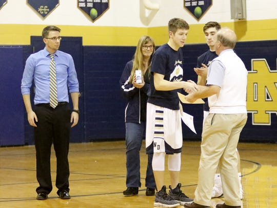Notre Dame boys basketball coach Bill Hopkins presents Crusaders senior Cullen McWhorter a certificate of recognition for helping to save the life of Gary Raupers on Dec. 12 before a game at Notre Dame. Also pictured, from left, are Notre Dame JV coach Max Young, Wendi Raupers and Gary Raupers II. Young was also honored for helping to save the life of the older Raupers.