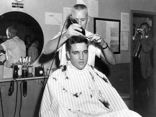 Elvis Presley gets his hair shorn before entering the U.S. Army at Fort Chaffee in Barling, Ark., on March 24, 1958.