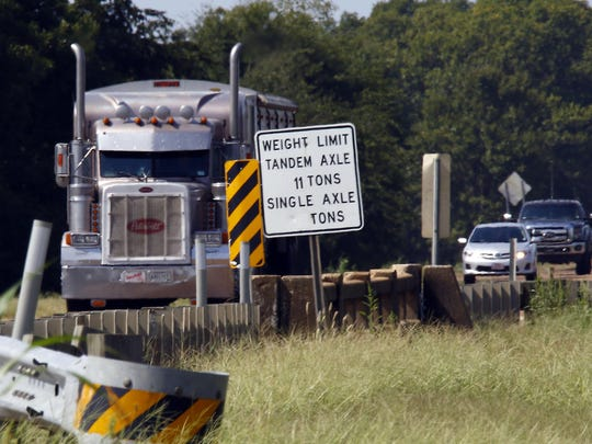In this Sept. 11, 2015 photo, a commercial truck passes over the bridge at Bobo Bayou on Mississippi Highway 6, near Batesville, Miss. The sign on the bridge shows the weight limitations established by the state for commercial and farm vehicles, but overuse, illegal heavier loads and increased traffic have taken their toll on this and many other of the state's bridges. The state of Mississippi's roads and bridges are an election issue this fall.