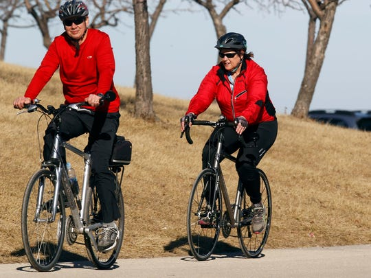 Bikers joined walkers, runners and others enjoying an access road behind the Marcus Amphitheater near Lakeshore State Park Saturday, as temperatures in Milwaukee hit the 60s.