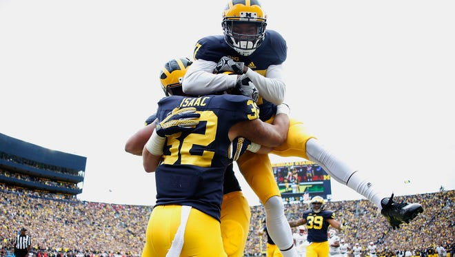 Ty Isaac #32 of the Michigan Wolverines celebrates a second quarter touch down with Freddy Canteen #17 while playing the UNLV Rebels on September 19, 2015 at Michigan Stadium in Ann Arbor, Michigan.
