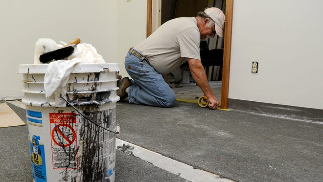 Lonnie Jones, with Lt D Painting, prepares the floor before he stains a new door Friday morning at the New Horizons new office on Kull Road in Lancaster.