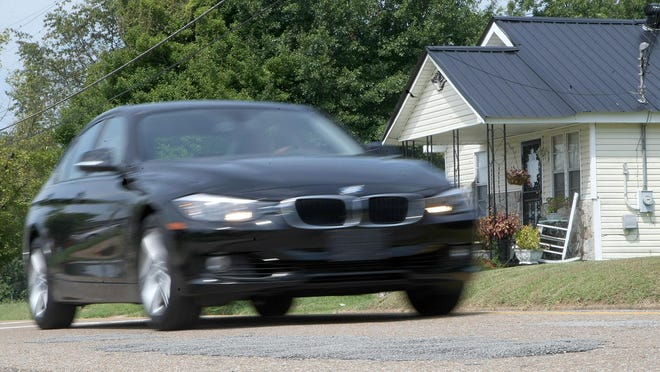 A vehicle drives near an area of patchwork repairs on Lane Avenue, near Jackson Central-Merry, Tuesday in Jackson.