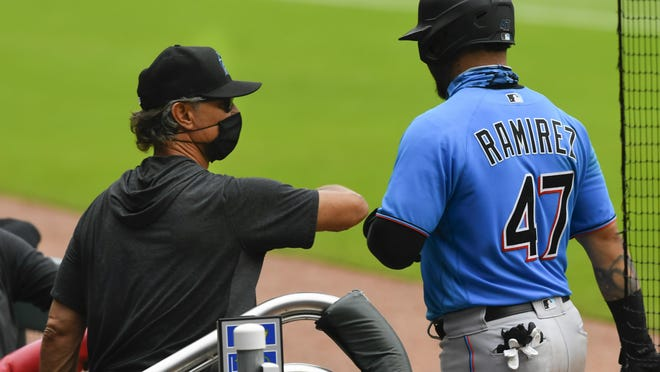 Marlins manager Don Mattingly congratulates the Marlins' Harold Ramirez (47) with an elbow bump as he enters the dugout after his two-run home run during a exhibition game last week. MLB has paused the Marlins' season due to a coronavirus outbreak