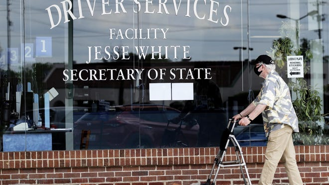 A man wears a mask as he looks at signs of a closed driver services facility in Deerfield on May 27.