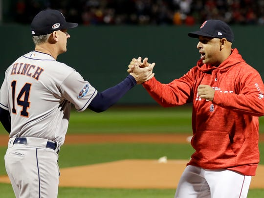 Houston Astros manager AJ Hinch, left, and Boston Red Sox manager Alex Cora shake Hanes before Game 1 of a baseball American League Championship Series on Saturday, Oct. 13, 2018, in Boston. (AP Photo/David J. Phillip)