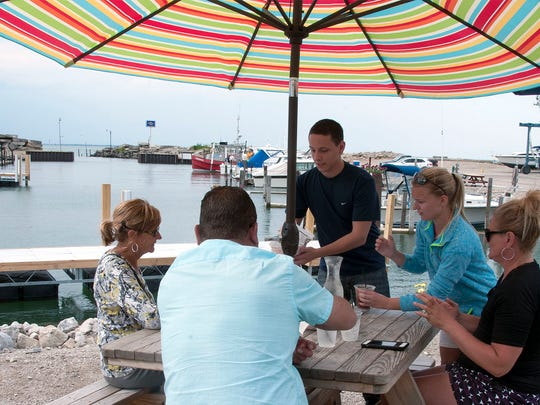 Hidden Beach Bar employees Dennis Tredel and Katie Schroeder serve up some appetizers and drinks to customers at the Danbury Township restaurant and bar at Schrock's Marina.