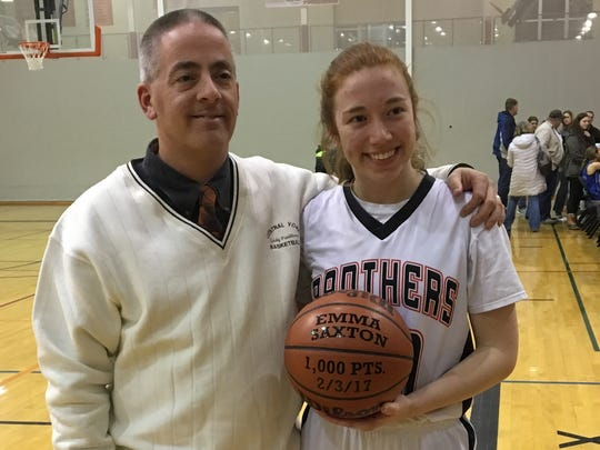 Central York's Emma Saxton, right, holds the game ball while posing with coach Scott Wisner after she scored her 1,000th career point during Friday's game against Spring Grove.