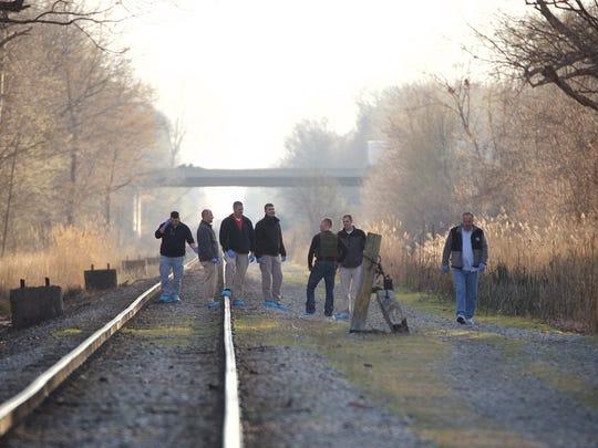 Investigators collect evidence around the scene where