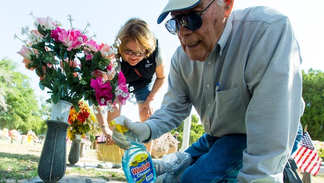 Precy Francia is joined by his daughter Mary Ann Francia, while cleaning the grave markers for his wife Carolina and his son Fernando on Monday, May 30, 2016, following the annual Memorial Day ceremony at Hillcrest Cemetery.