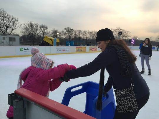 Jaymarie Torres of Camden helps her daughter Julianna, 6, onto the ice at WinterFest at Cooper River Park in  Pennsauken last winter.