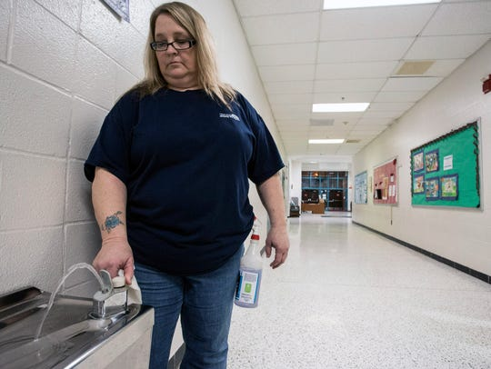Custodian Tammy Beisler sanitizes water fountains at
