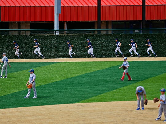 Little League teams from Springfield and Hollister warm up before competing in a short exhibition game during the ribbon-cutting ceremony of the Ballparks of America complex in Branson, Mo. on July 7, 2016.