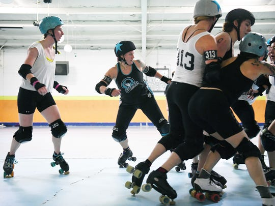 Playing as the jammer, Dixie Kicks tries to make her way through the other team's pack to score points during a scrimmage of the Blue Ridge Rollergirls at Sk8t Depot in Hendersonville on Wednesday, Oct. 11, 2017. The jammer for each team wears a star on her helmet and is the only skater that can score points.