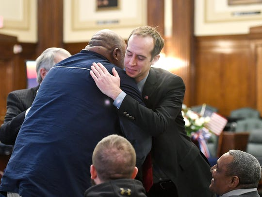 Eric D. Howard, the former Veterans Treatment Court coordinator, receives a hug from graduate of the program, U.S. Navy veteran Alex Watson before the start of the graduation ceremony at the Buncombe County Courthouse on Friday, Jan. 19, 2018.