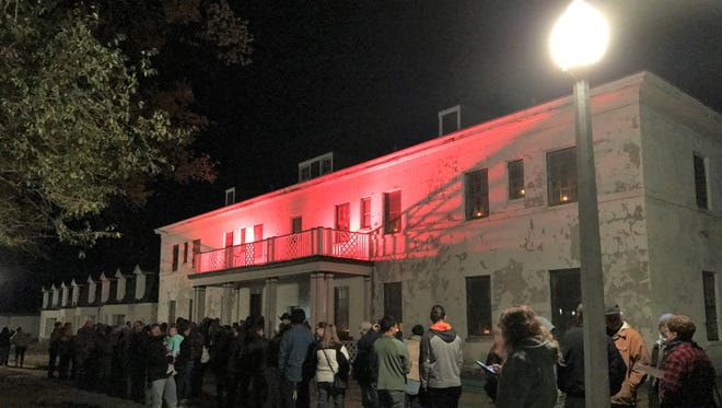 A crowd waits outside the marine hospital at the Fort Stanton Historic Site. The lighting set the mood.