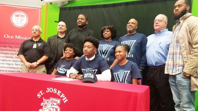 St. Joseph senior Qwahsin Townsel, center, seated, poses with family members and coaches after he signed his National Letter of Intent to attend Villanova on Wednesday morning.