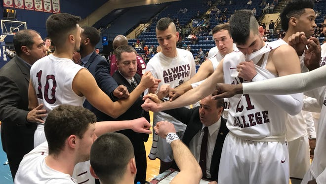 Coach Chuck McBreen (seated) and Ramapo in the huddle during the Final Four of the NCAA Division III Men's Basketball Championship in Salem, Va. on Friday, March 16, 2018.
