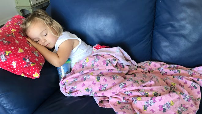 Isabella naps on the couch last week when she was home sick with strep throat.
