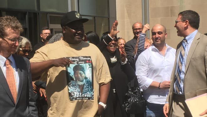 Antony Jakes (second to left) and Robert Bouto (second to right) walk out Leighton Criminal Court Building in Chicago on Monday after prosecutors agreed to dismiss convictions against the men for separate men in the early 1990s. The two men spent a combined 45 years incarcerated.