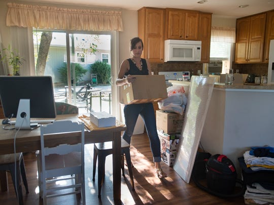 Jill Arnold piles boxes up as she and her boyfriend Levi Sanchez move out of their rental home of four years in west Fort Collins on Wednesday, July 11, 2018. The couple are moving into their own home after searching for high and low for something in their budget.