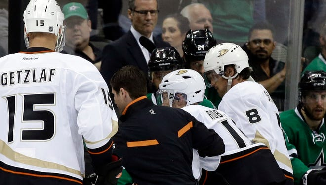 Anaheim Ducks' Ryan Getzlaf watches as Stephane Robidas, third from left, is helped off the ice with a broken leg.